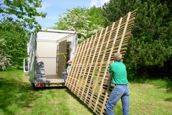 Flyttefolk løfter del til kolonihavehus ind på trailer.